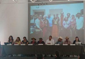 Conferencia de prensa, al fondo imagen de la visita del GT, Oaxaca 2016